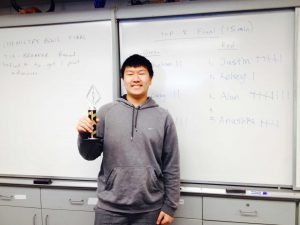 Sophomore Alan Tan poses with trophy in front of scoreboard