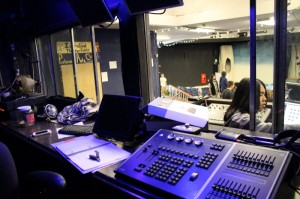 The interior of the sound booth behind Julian Chan at the sound board.