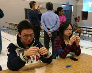 PC: Cathy Wang Caption: Freshman William Zhang and sophomore Connie Liang attempt to solve metal ring puzzles at the Pi Day Celebration.