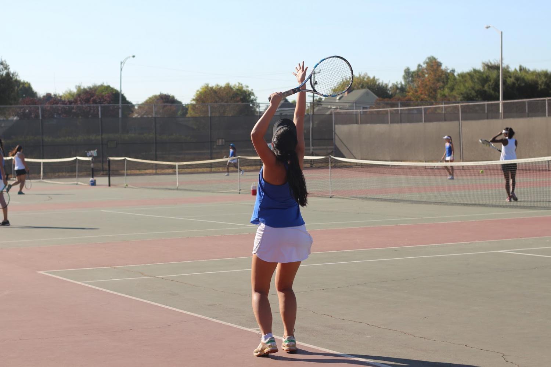 Varsity+member+Amanda+Tran+%2812%29+prepares+to+serve+in+her+singles+game.+