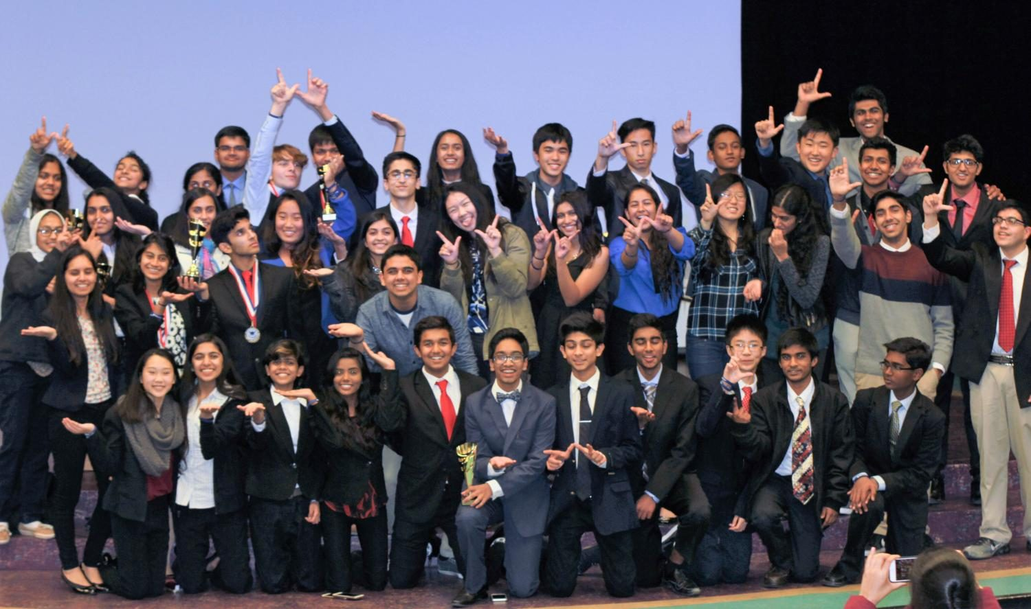 The+Irvington+Debate+Club+rejoices+with+their+trophies+after+the+invitational.