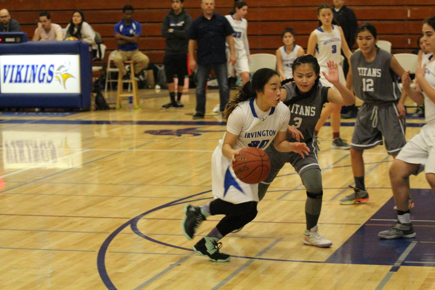 The+Kennedy+Titans+players+crowd+around+JV+Basketball+player+Kaitlyn+Kodama+%289%29+as+she+attempts+to+score+a+basket.