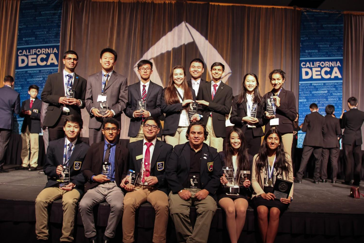 Irvington+DECA+students%2C+along+with+advisors+Mr.+Ballado+and+Greg+Chi%2C+pose+with+their+well-deserved+plaques.