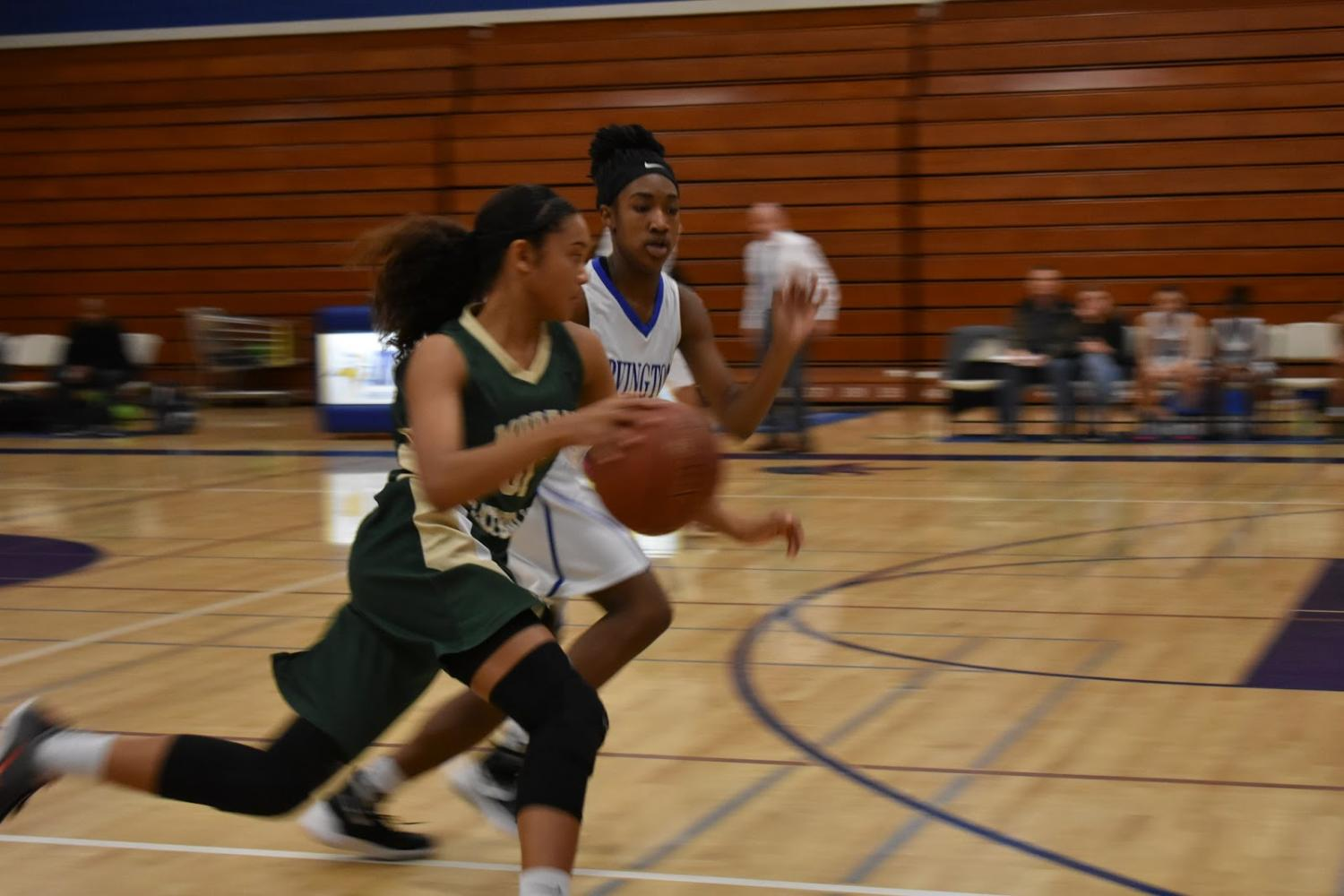 Sophomore+Alexis+Early+runs+alongside+a+Moreau+basketball+player+to+try+and+intercept+the+ball.%0A