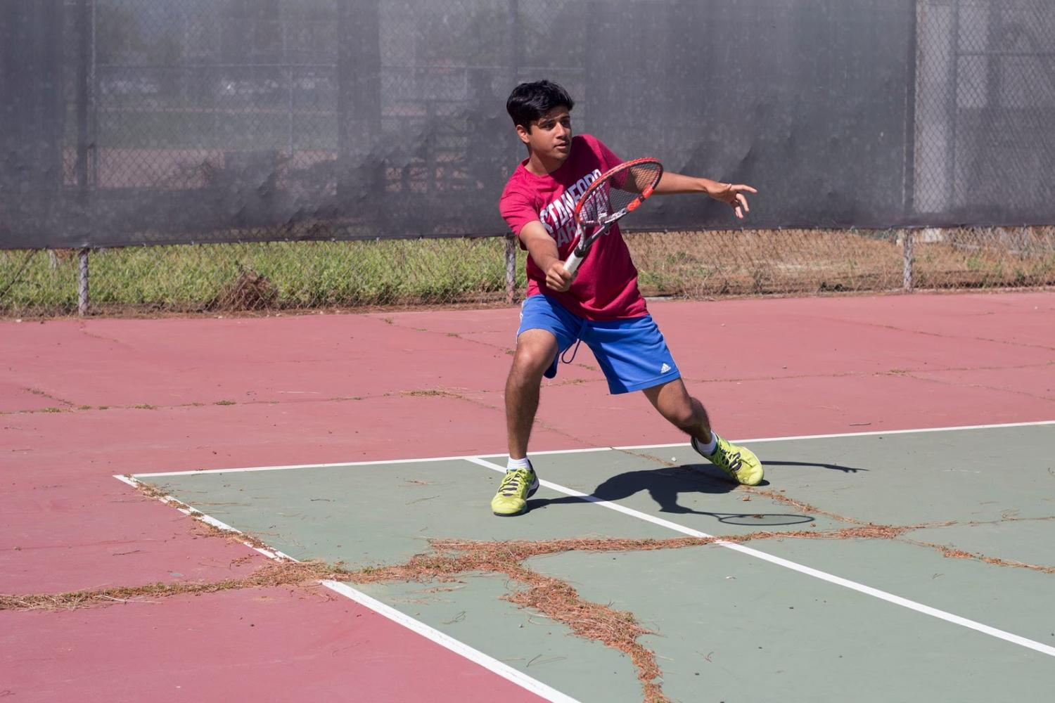 Co-captain Jay Pandit (12),  a varsity singles player finishes a forehand during practice, stepping over the numerous cracks on the courts that haven't been resurfaced in 20 years.