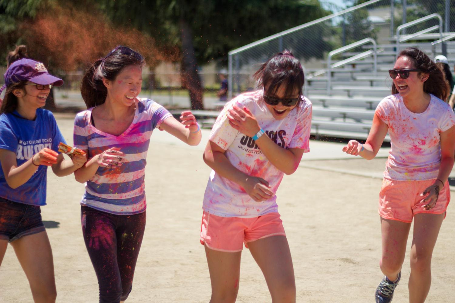Sophomores Saisha Singh, Mary Tang, Hannah Limary, and Simone Mendoza throw color at one another while running around the track.