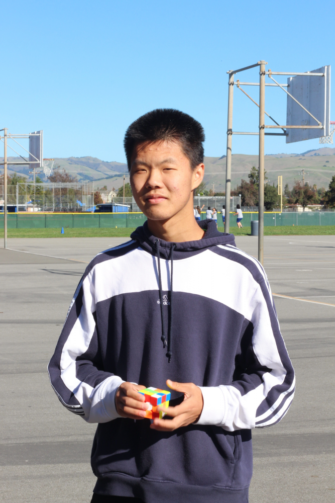 Zili pops his normal 3 by 3 cube out of his pocket and nonchalantly solves it a few times as he poses for his picture.