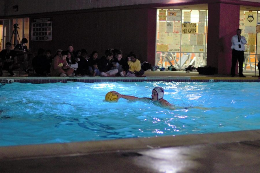 Captain Cade Ross (12) swims up the pool with the ball.