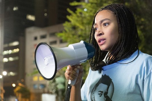 Amandla Stenberg as Starr Carter advocating for African-American rights in a protest.