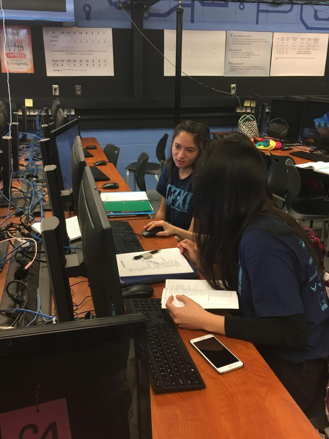 Samantha Bustamante (12) and other members of the girls' teams practicing for the competition at a computer.