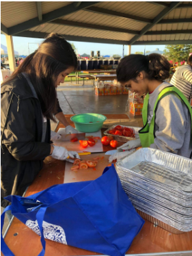 Vivian Ku (12) and Afra Raza (12) help chop vegetables.
