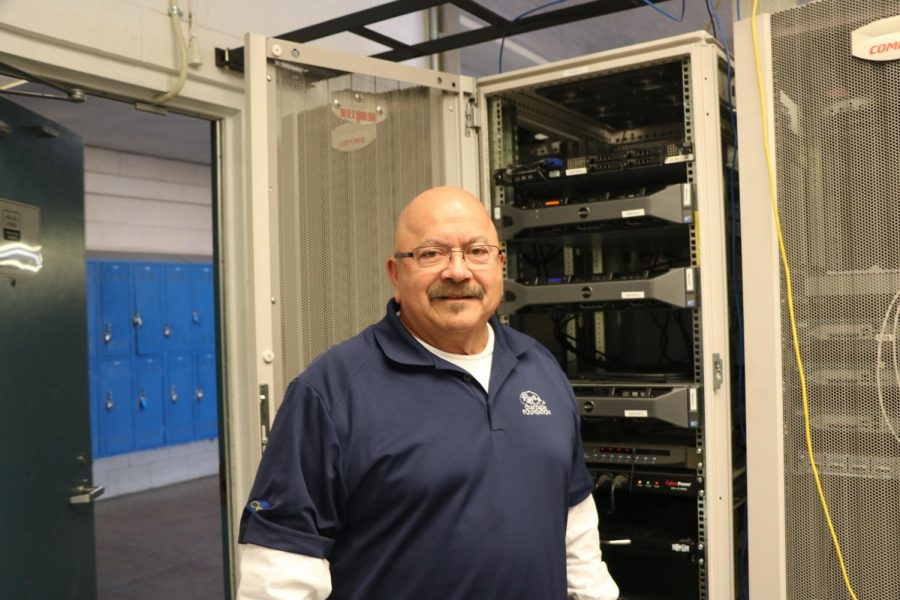 Mr. Albizo, who has been teaching courses related to internet engineering at Irvington for ten years, poses in front of various routers and switches, which are essential to running networks.