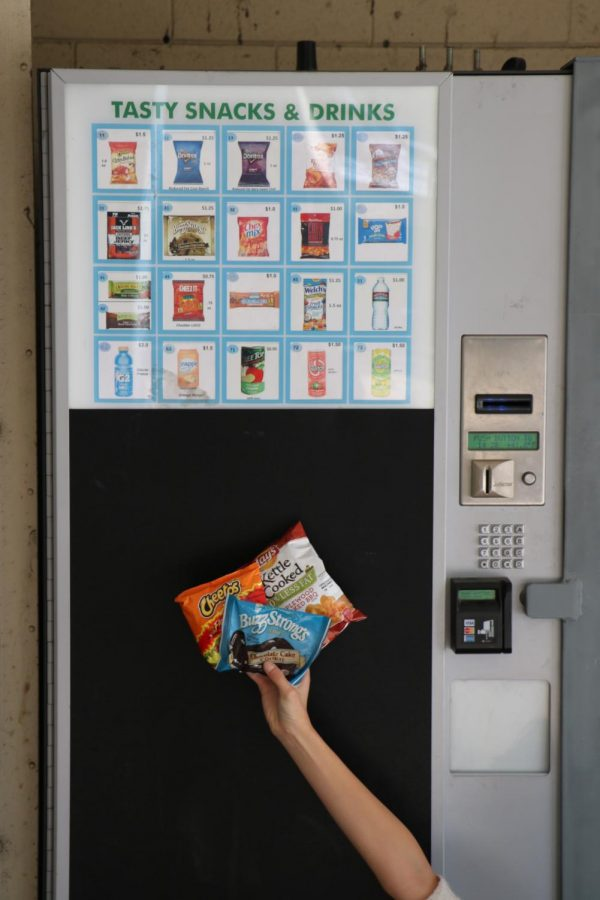The top three snacks, Buzz Strong's chocolate chip cookie, hot Cheetos, and kettle cooked potato chips in front of the vending machine they came from.