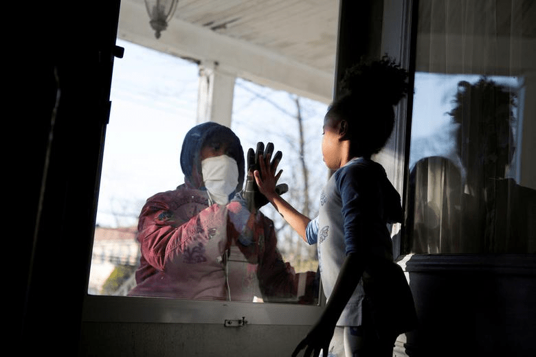 An+essential+worker+in+the+healthcare+industry+meets+his+daughter+through+a+glass+window+while+maintaining+a+safe+distance+to+protect+his+family+from+coronavirus.+