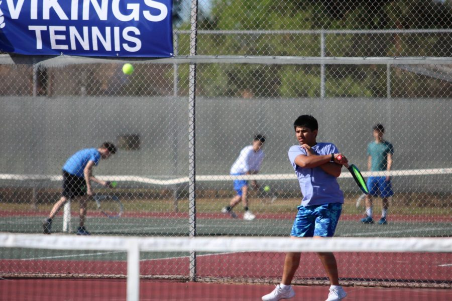 Team Captain Aryaman Gautam (11) hits a forehand. This photo was taken last season, pre-COVID.