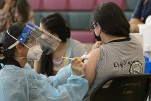 FILE - In this May 27, 2021, file photo, sisters Guadalupe Flores, 15, right, and Estela Flores, 13, left, from East Los Angeles, get vaccinated with the Pfizers COVID-19 vaccine by licensed vocational nurse Rita Orozco, far left, at the Esteban E. Torres High School in Los Angeles. The Los Angeles board of education is expected to vote Thursday, Sept. 9, on whether to require all students 12 and older to be fully vaccinated against the coronavirus to participate in on-campus instruction in the nations second-largest school district. (AP Photo/Damian Dovarganes, File)